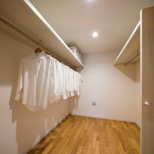 Small scandinavian u-shaped laundry cupboard in Tokyo with beaded inset cabinets, white cabinets, white walls, plywood floors and brown floor.