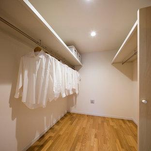 Ispirazione per un piccolo ripostiglio-lavanderia scandinavo con ante a filo, ante bianche, pareti bianche, pavimento in compensato e pavimento marrone