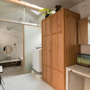他の地域のコンテンポラリースタイルのおしゃれなランドリールーム (落し込みパネル扉のキャビネット、中間色木目調キャビネット、グレーの壁、グレーの床) の写真