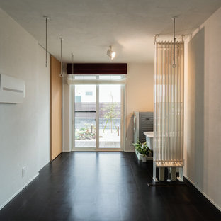 Example of a trendy cork floor and black floor laundry room design in Other with white walls