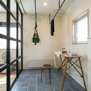 Bild på en liten industriell tvättstuga enbart för tvätt, med vita väggar, klinkergolv i keramik och blått golv