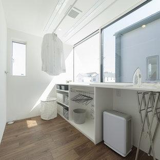 Réalisation d'une buanderie minimaliste dédiée avec un mur blanc, un sol en bois foncé, un sol marron et un plan de travail blanc.