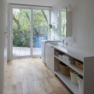 Idées déco pour une buanderie linéaire moderne avec un évier intégré, un placard sans porte, des portes de placard blanches, un mur blanc, un sol en bois brun, un sol marron et un plan de travail blanc.