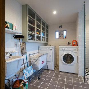 東京23区のI型地中海スタイルの洗濯室の画像 (シングルシンク、ガラス扉のキャビネット、白い壁、セラミックタイルの床、グレーのキャビネット)