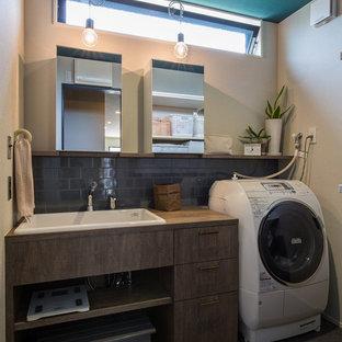 Inspiration för asiatiska tvättstugor, med släta luckor, grå skåp, vita väggar och grått golv