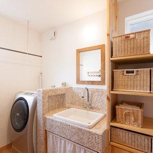 Réalisation d'une buanderie asiatique avec un placard sans porte, un mur blanc, un sol en bois brun et un sol marron.
