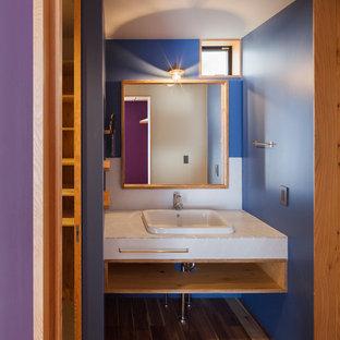 Идея дизайна: маленькая линейная прачечная в стиле рустика с накладной раковиной, деревянной столешницей, синими стенами, темным паркетным полом, со скрытой стиральной машиной, коричневым полом и белой столешницей
