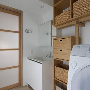 Idées déco pour une buanderie linéaire asiatique avec un évier intégré, un placard sans porte, des portes de placard en bois brun, un mur blanc et un sol beige.