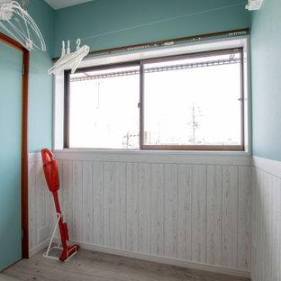 Inredning av en maritim liten tvättstuga enbart för tvätt, med blå väggar, plywoodgolv och beiget golv