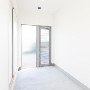 Exempel på en tvättstuga, med vita väggar, betonggolv och grått golv