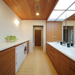 Inredning av en modern tvättstuga, med en integrerad diskho, släta luckor, skåp i mellenmörkt trä, vita väggar och brunt golv