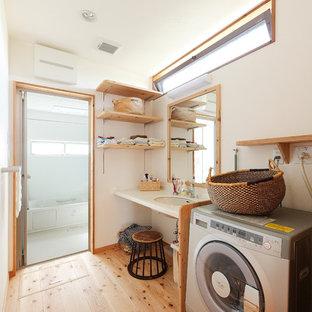 Inredning av en asiatisk tvättstuga, med vita väggar, mellanmörkt trägolv, brunt golv och en undermonterad diskho