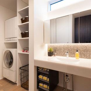 Идея дизайна: прачечная в стиле модернизм с открытыми фасадами, белыми стенами, деревянным полом, с сушильной машиной на стиральной машине, коричневым полом, белой столешницей и врезной раковиной