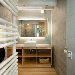 Aménagement d'une buanderie linéaire asiatique multi-usage et de taille moyenne avec un placard sans porte, des portes de placard en bois brun, un mur gris, un sol en bois brun et des machines dissimulées.