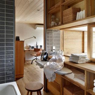 他の地域の北欧スタイルのおしゃれなランドリールーム (オープンシェルフ、中間色木目調キャビネット、グレーの壁、茶色い床) の写真