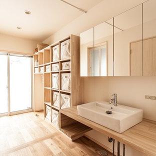 Cette photo montre une petite buanderie linéaire moderne dédiée avec un placard sans porte, des portes de placard en bois clair, un plan de travail en bois, un mur blanc et un sol en bois brun.