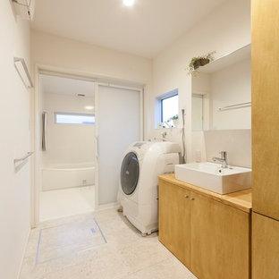 Foto på en minimalistisk tvättstuga, med vita väggar och vitt golv