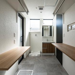 Modern inredning av en linjär tvättstuga med garderob, med vita väggar, vinylgolv och grått golv