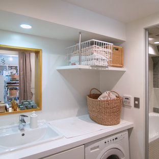 Inspiration for a mid-sized traditional single-wall utility room in Tokyo with a drop-in sink, flat-panel cabinets, white cabinets, white walls, medium hardwood floors and an integrated washer and dryer.