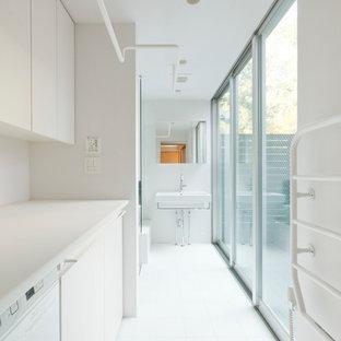 Idée de décoration pour une buanderie linéaire minimaliste dédiée avec un placard à porte plane, des portes de placard blanches, un mur blanc, un sol en carrelage de céramique et des machines dissimulées.