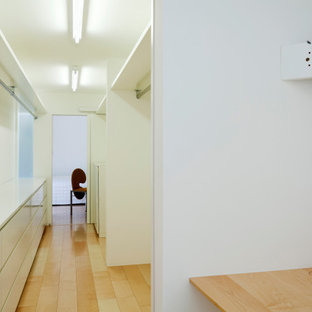 Cette photo montre une buanderie parallèle moderne avec un mur blanc, un sol en bois peint, un sol beige, un plafond en poutres apparentes, du lambris de bois, un placard, un évier encastré, un placard à porte plane, des portes de placard blanches, un plan de travail en stratifié, le lave-linge et le sèche-linge forment un seul appareil électroménager et un plan de travail blanc.