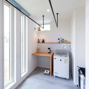 Foto på en linjär tvättstuga enbart för tvätt, med vita väggar, vinylgolv och grått golv