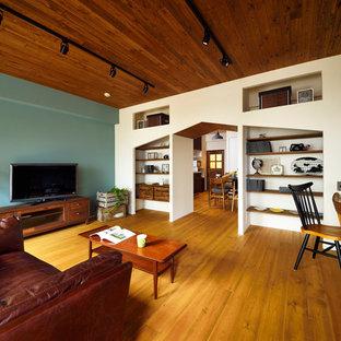 他の地域の北欧スタイルのおしゃれな独立型リビング (マルチカラーの壁、無垢フローリング、据え置き型テレビ、茶色い床) の写真
