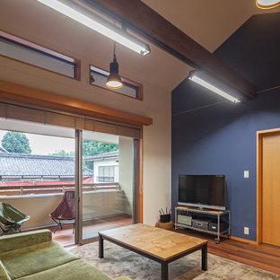Inredning av ett asiatiskt vardagsrum, med flerfärgade väggar, mellanmörkt trägolv, en fristående TV och brunt golv