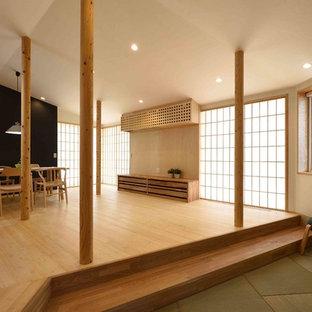 他の地域の大きいラスティックスタイルのおしゃれなリビング (白い壁、竹フローリング、暖炉なし、壁掛け型テレビ、ベージュの床) の写真