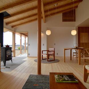 他の地域の中サイズのおしゃれなLDK (白い壁、淡色無垢フローリング、薪ストーブ、石材の暖炉まわり、据え置き型テレビ、茶色い床) の写真