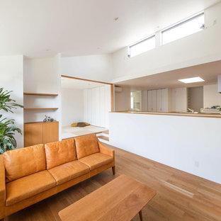 他の地域のモダンスタイルのおしゃれなLDK (白い壁、合板フローリング、据え置き型テレビ、茶色い床) の写真