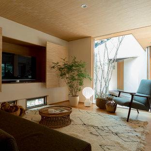 Diseño de salón moderno, sin chimenea, con paredes beige, suelo de madera clara y televisor colgado en la pared