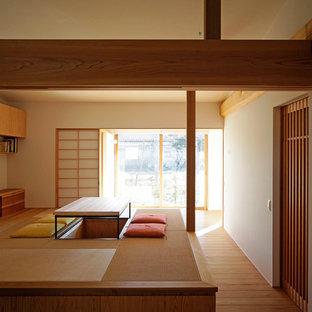 Inredning av ett asiatiskt vardagsrum, med vita väggar, tatamigolv, en fristående TV, brunt golv och ett finrum