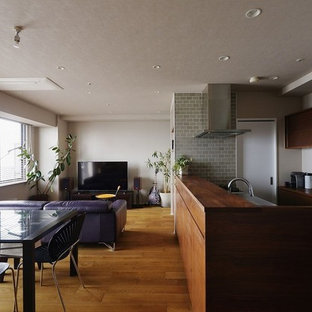アジアンスタイルのおしゃれなLDK (白い壁、無垢フローリング、据え置き型テレビ、茶色い床) の写真