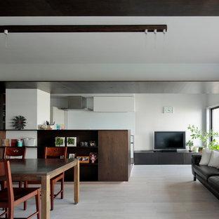 Modelo de salón abierto, moderno, con paredes blancas, suelo de contrachapado, televisor independiente y suelo beige