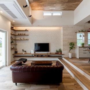 Foto di un grande soggiorno etnico aperto con pavimento in legno massello medio, pareti bianche, TV a parete, pavimento beige e pareti in legno