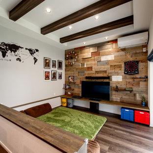 Mittelgroßes, Offenes Wohnzimmer mit braunem Holzboden, Tapetendecke und Tapetenwänden in Sonstige