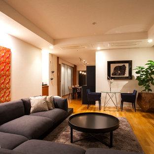 東京23区のアジアンスタイルのおしゃれなLDK (白い壁、無垢フローリング、据え置き型テレビ、オレンジの床) の写真