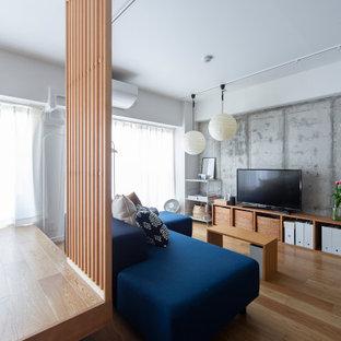 Cette image montre un petit salon urbain ouvert avec un mur blanc, un sol en bois brun, aucune cheminée, un sol marron, un plafond en papier peint et du papier peint.