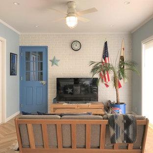 他の地域の小さいトロピカルスタイルのおしゃれなリビング (マルチカラーの壁、淡色無垢フローリング、据え置き型テレビ、ベージュの床) の写真