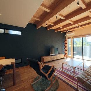 Inspiration pour un petit salon asiatique avec un mur noir, un téléviseur indépendant, un sol en contreplaqué, aucune cheminée et un sol marron.