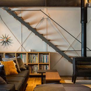 他の地域の中くらいのコンテンポラリースタイルのおしゃれなLDK (ミュージックルーム、白い壁、塗装フローリング、薪ストーブ、コンクリートの暖炉まわり、据え置き型テレビ、茶色い床、表し梁、板張り壁) の写真
