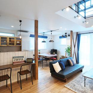 他の地域の広いカントリー風おしゃれなLDK (白い壁、無垢フローリング、コーナー設置型暖炉、木材の暖炉まわり、マルチカラーの床) の写真