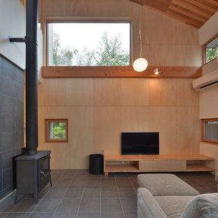 名古屋のアジアンスタイルのおしゃれなLDK (薪ストーブ、茶色い壁、据え置き型テレビ、グレーの床) の写真