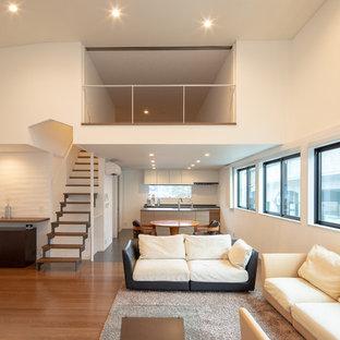 東京23区の広いモダンスタイルのおしゃれなLDK (白い壁、淡色無垢フローリング、据え置き型テレビ、茶色い床) の写真