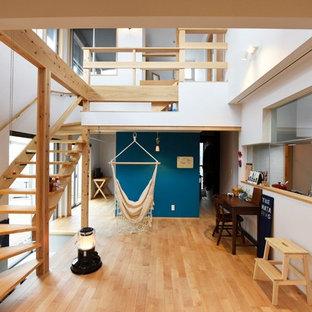 他の地域のアジアンスタイルの居間の画像 (青い壁、淡色無垢フローリング、茶色い床)