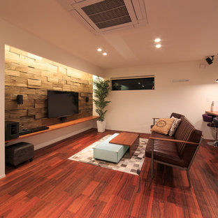 This is an example of a contemporary enclosed living room in Other with white walls, painted wood floors, a wall-mounted tv and red floor.