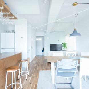 東京23区のビーチスタイルのおしゃれなLDK (白い壁、無垢フローリング、据え置き型テレビ、茶色い床) の写真