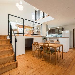 Modelo de salón abierto, de estilo zen, sin chimenea, con parades naranjas, suelo de madera en tonos medios, televisor independiente y suelo beige