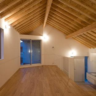 Idee per un piccolo soggiorno moderno stile loft con sala formale, pareti arancioni, pavimento in compensato, nessun camino e pavimento marrone